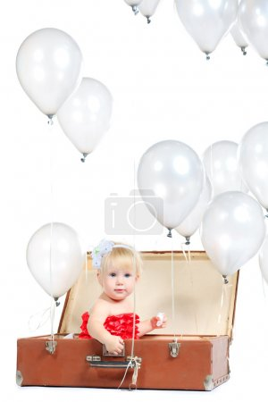 Photo for Little girl is sitting in the old suitcase under many balloons. Isolated over white. - Royalty Free Image