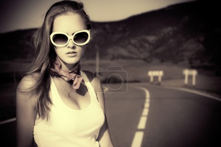 Photo for Black-and-white portrait of a beautiful young woman posing on a road over picturesque landscape. - Royalty Free Image