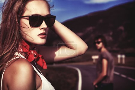 Photo for Couple of modern young posing on a road over picturesque landscape. - Royalty Free Image