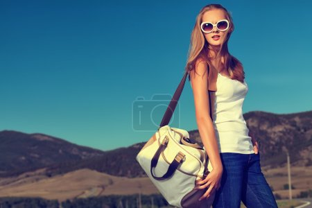 Photo for Beautiful young woman posing on a road over picturesque landscape. - Royalty Free Image