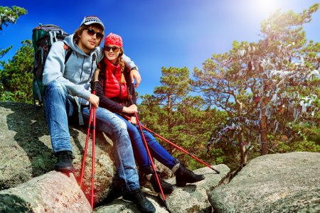 Photo for Couple of tourists are sitting at the top of a mountain with a feeling of freedom. - Royalty Free Image