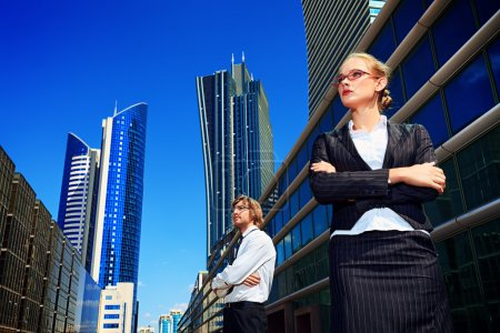 Photo for Business woman and business man standing in front of skyscrapers. - Royalty Free Image