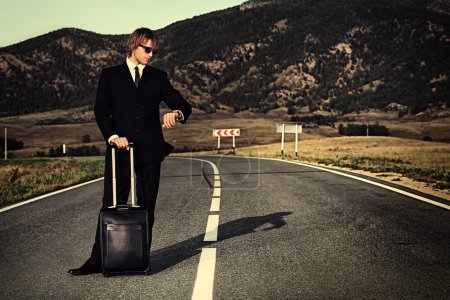Photo for Handsome business man standing on a highway with his suitcase and looking at his watch. - Royalty Free Image