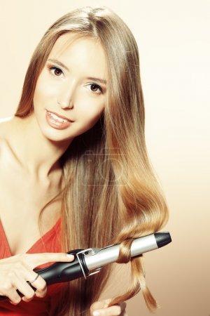 Photo pour Belle jeune femme faisant coiffure avec des fers à friser . - image libre de droit