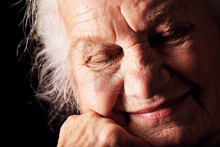 Photo pour Portrait d'une femme âgée rêveuse assise les yeux fermés. Sur fond noir . - image libre de droit