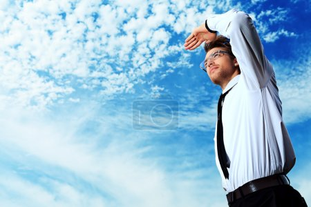 Photo for Successful business man standing over blue sky and purposefully looking away. - Royalty Free Image