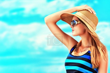 Photo for Happy young woman posing over blue sky. - Royalty Free Image