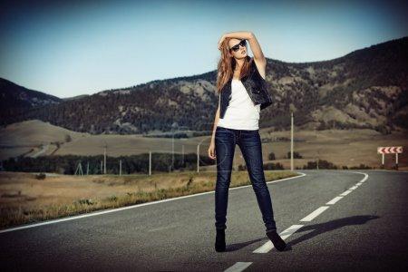 Photo pour Portrait complet d'une belle jeune femme posant sur une route au-dessus d'un paysage pittoresque . - image libre de droit