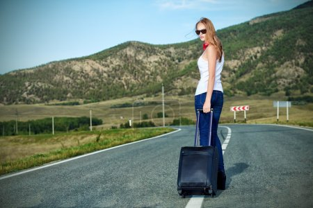 Photo for Attractive young woman hitchhiking along a road. - Royalty Free Image
