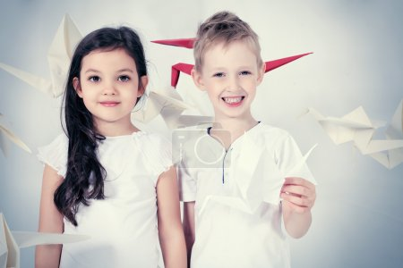 Photo for Happy kids standing together surrounded by paper birds. Dream world. - Royalty Free Image