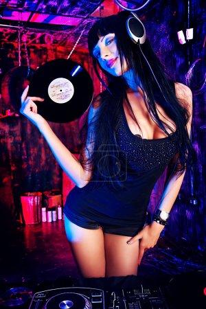 Photo pour Belle fille DJ sexy travaillant sur une fête dans le vieux garage . - image libre de droit