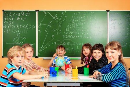 Photo pour Groupe d'écoliers qui étudient en classe . - image libre de droit