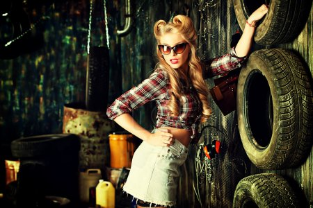 Photo for Charming pin-up woman with retro hairstyle and make-up in the old garage. - Royalty Free Image