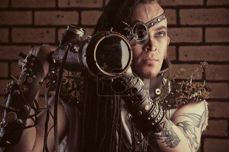 Photo pour Portrait d'un homme de steampunk avec un dispositifs mécaniques sur mur de briques. - image libre de droit