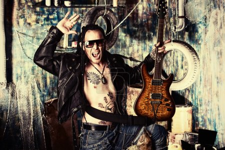 Photo for Heavy metal musician is playing electrical guitar in the old garage. - Royalty Free Image