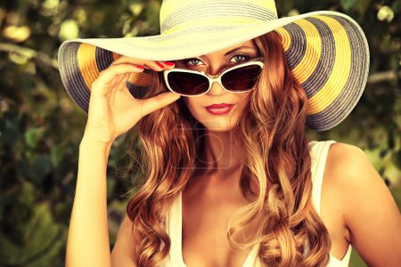 Photo for Beautiful young woman in elegant hat and sunglasses posing outdoor. - Royalty Free Image