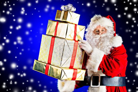 Photo for Portrait of a traditional Santa Claus with Christmas gifts. Over dark background. - Royalty Free Image