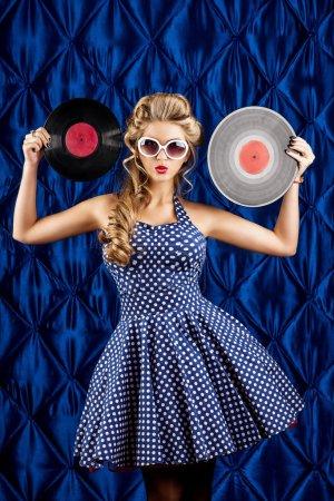 Foto de Mujer muy pin-up con retro peinado y maquillaje posando con disco de vinilo sobre fondo vintage. - Imagen libre de derechos