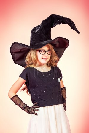 Photo for Pretty ten years girl in a witch costume smiling at camera. Pink background. Halloween. - Royalty Free Image