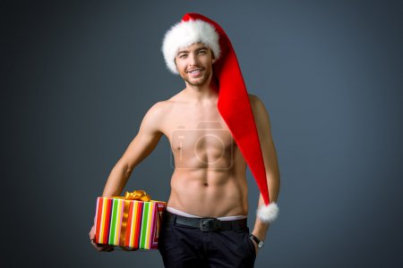 Photo for Sexual young man in Christmas hat holding a gift. - Royalty Free Image