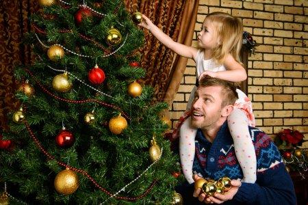 Photo pour Heureux père et sa petite fille décorant le sapin de Noël à la maison . - image libre de droit