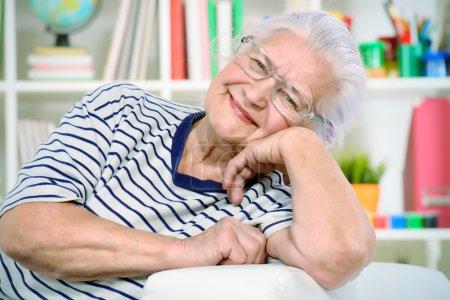 Photo pour Femme âgée souriante assise à la maison sur un canapé . - image libre de droit