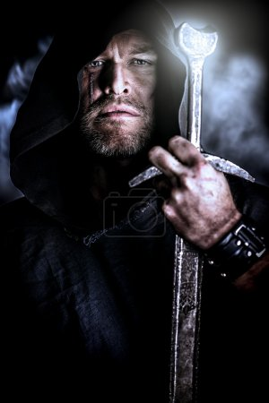 Photo for Portrait of a courageous warrior wanderer in a black cloak and sword in hand. Historical fantasy. - Royalty Free Image