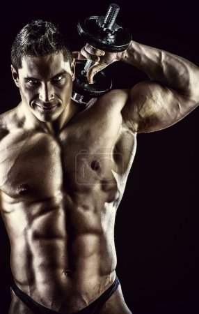 Photo for Portrait of a handsome muscular bodybuilder posing over black background. - Royalty Free Image