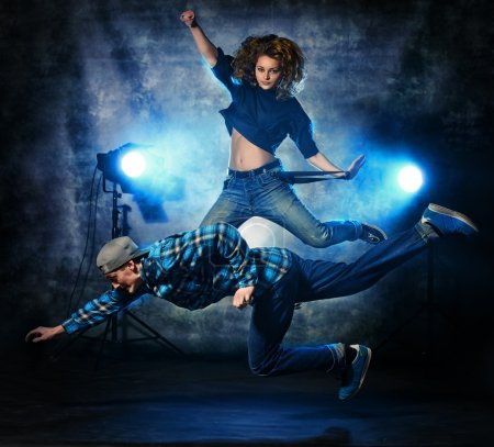 Photo for Two modern dancers jumping over grunge background. Hip-hop. Urban, disco style. - Royalty Free Image