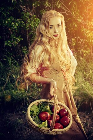 Photo pour Beautiful young woman with magnificent blonde hair standing outdoor with a basket with apples. Countryside. - image libre de droit
