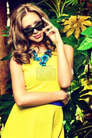 Photo pour Jolie jeune femme parmi les plantes tropicales. Des vacances. Les tropiques. Coup de mode. - image libre de droit