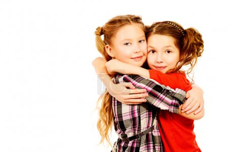 Foto de Two smiling girls embracing each other like best friends. Isolated over white. - Imagen libre de derechos