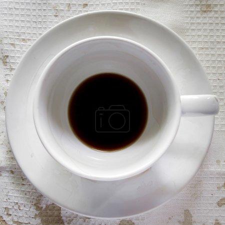 Photo pour Tasse de café sur fond de nappe blanche. lie dans le fond de la tasse. - image libre de droit