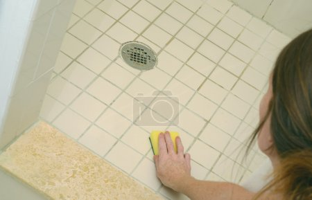 Woman scrubbing soap scum from a dirty shower floo...