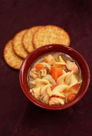 Photo pour Nourriture réconfortante et soupe de nouilles au poulet dans un bol rouge - image libre de droit