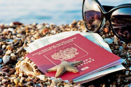 Photo pour Toujours en voyage avec un passeport russe dans le sable sur la plage - image libre de droit