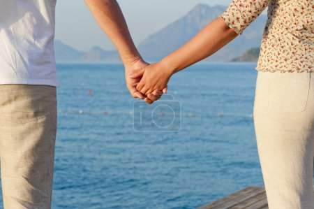 Photo for Loving couple holding hands on the background of the sea - Royalty Free Image