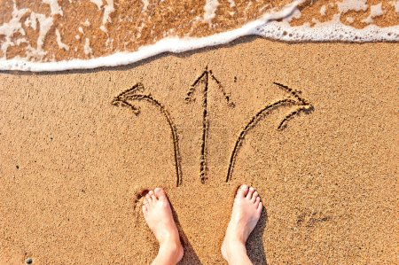 Photo pour Pieds nus des hommes dans le sable et les flèches - image libre de droit