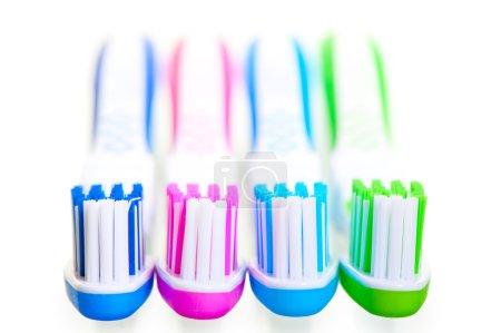 Photo pour Quatre nouvelles brosses à dents multicolores sont sur fond blanc - image libre de droit