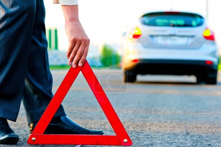 Photo for Man sets the warning triangle - Royalty Free Image
