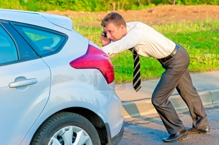 Businessman pushing a car and talking on the phone