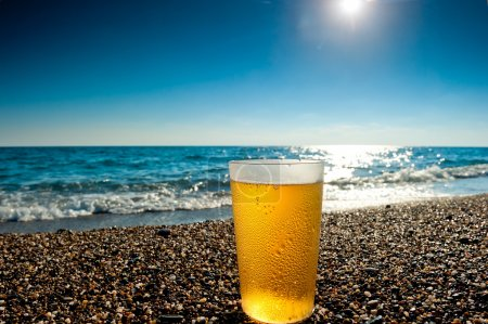 glass of cold beer on a background of the sea