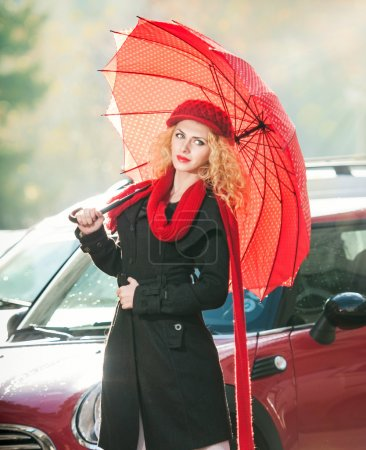 .Beautiful fashionable young girl with red umbrella in the street