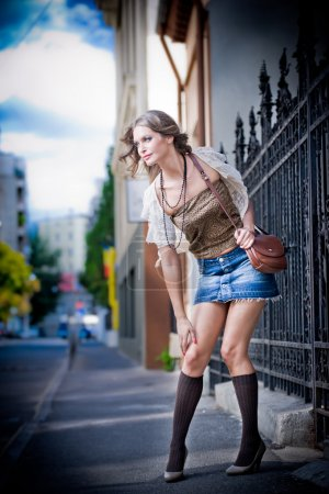 girl short skirt and bag walking on street.Young European Girl in Urban Setting.sexy woman dressed provocatively and posing on street.Blonde attractive woman with interesting hair walking in the city