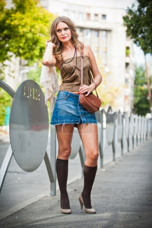 Fashion girl with short skirt , bag and high heels walking on street.attractive woman with interesting hair walking in the city.Walking fashion model in blue short skirt with long sexy legs