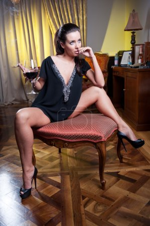 Beautiful sexy woman with glass of wine thinking. Looking away. Portrait of a woman with long legs posing challenging .Brunette sexy woman sitting in wood chair and drinking in a vintage scene