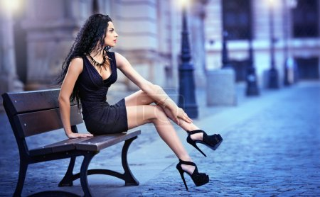 Handsome attractive girl wearing short skirt and high heels standing outside in urban scene.Fashion model in blue short skirt with long sexy legs on the street .Woman sitting on bench in the city
