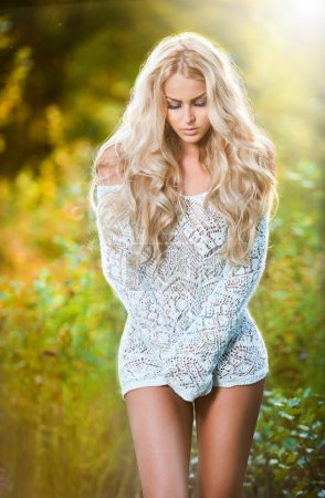 Portrait of a sensual young blonde female on field in sexy outfit
