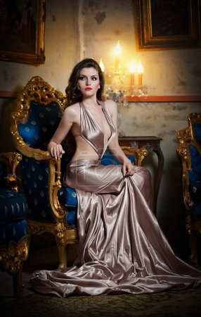 Young beautiful luxurious woman in long elegant dress. Beautiful young woman in a luxurious classic interior. Seductive brunette woman in luxury manor, vintage style
