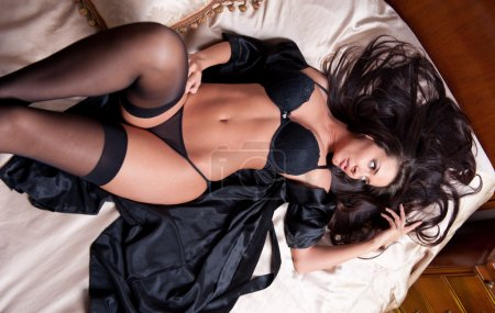 Beautiful and sexy brunette young woman wearing black lingerie in bed. Fashion shoot lingerie indoor. Sexy young girl in black lingerie in hotel